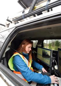 Photo of Huron Geomatics engineer working on a computer in the mobile LiDAR mapping vehicle.