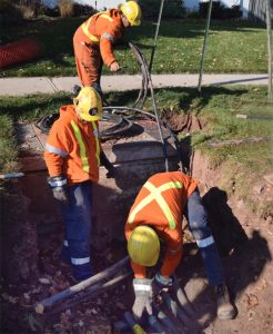 Photo of El-Con Construction Inc. work crews installing buried cable system in residential neighbourhood.