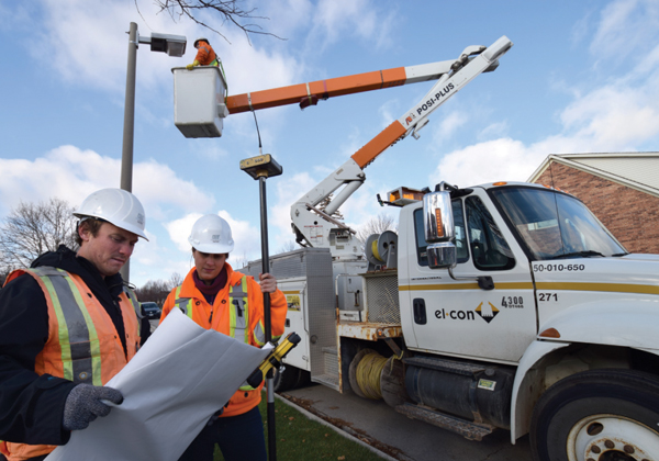 Photo of El-Con Construction Inc. work crews performing overhead streetlight maintenance using aerial lift truck with UTS Consultants Inc. engineers reviewing drawings in foreground.