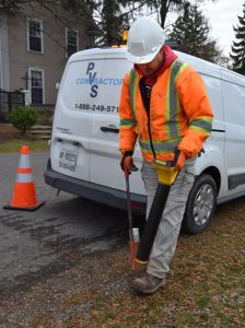 Photo of PVS Contractors employee performing underground locate on a residential boulevard.